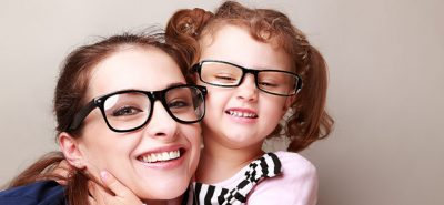 Happy young mother and lauging kid in fashion glasses hugging